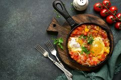 Shakshuka - eggs in tomato sauce.Top view with copy space. Royalty Free Stock Photo