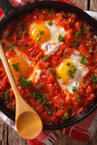 Shakshuka fried eggs macro in a frying pan. vertical top view Royalty Free Stock Photo