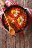 Shakshuka frukost av stekte ägg och tomater i en panna Vertica Royaltyfri Fotografi