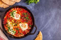 Shakshuka in a Frying Pan. Eggs Poached in Spicy Tomato Pepper Sauce royalty free stock photo