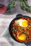 Shakshuka is a tasty dish of eggs, fried in a sauce of tomatoes, hot pepper, onion and seasonings on a black cast-iron pan. Tomato royalty free stock photos