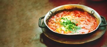 Shakshuka. Traditional jewish food and middle eastern cuisine recipe. Fried eggs, tomatoes, bell pepper and parsley in a. Pan. Close up, selective focus. Tonnen Stock Photos