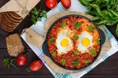 Shakshuka - un plat des oeufs sur le plat à une sauce des tomates, du piment, des oignons et des assaisonnements Photo libre de droits