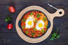 Shakshuka - un plat des oeufs sur le plat à une sauce des tomates, du piment, des oignons et des assaisonnements Photos stock