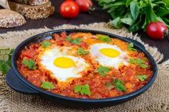 Shakshuka - un plat des oeufs sur le plat à une sauce des tomates, du piment, des oignons et des assaisonnements Images stock