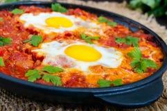 Shakshuka - un plat des oeufs sur le plat à une sauce des tomates, du piment, des oignons et des assaisonnements Images libres de droits