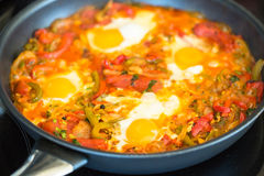 Shakshuka vegetable and egg middle eastern dish cooking. Shakushuka a savory egg meal cooking in a frying pan. It contains peppers, tomatoes, eggs, onions and Stock Image