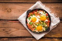 Shakshuka z jajkami, pomidorem i pietruszką w żelaznej niecce, Shakshuk Obrazy Stock