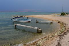 Shaky wooden molos and fisherman boats on beach in Croatia during cloudy day before the rain Royalty Free Stock Image