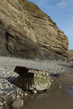 Shale rock cliff. Geological feature, striated shale and mud-stone cliff on a beach with pebble and a water smoothed boulder on the sand Stock Image
