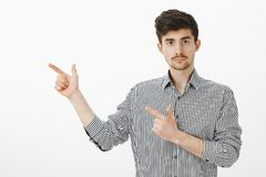 Shall we go. Portrait of confident serious young male coworker in striped shirt, pointing with finger gun gestures left. Staring focused at camera, suggesting Royalty Free Stock Photo