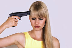 Shall I shoot myself?. Woman puts gun to her head with depressed look Royalty Free Stock Photography