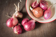 Shallots with bowl on table. Royalty Free Stock Photo