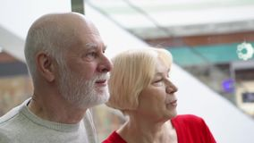Shallow depth of field. Focus on senior man. Happy senior couple riding elevator up in modern mall