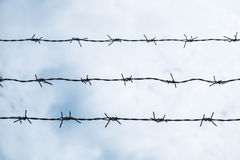 Shallow depth of field, old barbed steel wire against blue sky Royalty Free Stock Photos