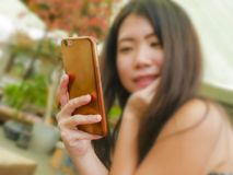 Shallow depth of focus hand with mobile phone of young beautiful and happy Asian Korean woman smiling cheerful enjoying relaxed ou. Tdoors at sweet coffee shop royalty free stock photo