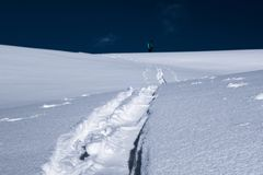 Ski touring track in powder snow with blurred skier background Royalty Free Stock Photography