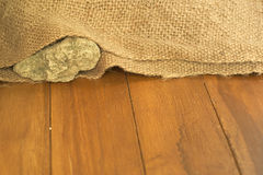 Shallow DOF of rock inside old sack. Concept of stupid kind of hard work Royalty Free Stock Photography