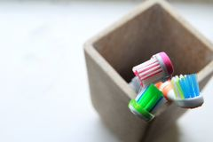Shallow DOF shot of three toothbrushes in a clay tumbler in the morning light stock photo
