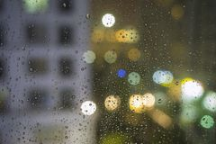 Shallow DOF of water drops on glass with bokeh and apartment building on background.  Royalty Free Stock Image