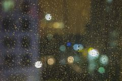 Shallow DOF of water drops on glass with bokeh and apartment building on background.  Stock Photo