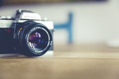 Shallow Focus Photo of Dslr Camera on Brown Wooden Table Stock Photos