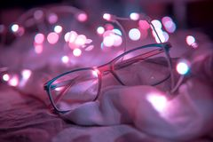 Shallow Focus Photography of Blue-framed Eyeglasses Near String Lights Royalty Free Stock Photo