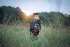Shallow Focus Photography of Boy Standing on Green Grass Holding Camera royalty free stock images