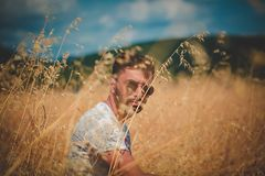 Shallow Focus Photography of Man in Gray Top Sitting on Brown Grass stock image