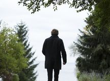 Shallow Focus Photography of Man Wearing Black Coat and Black Pants Standing Beside Green Trees Stock Photo