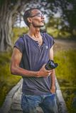 Shallow Focus Photography of Man Wearing Gray T-shirt Holding Dslr Camera Lens Stock Image