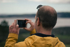 Shallow Focus Photography of Man in Yellow Jacket Holding White Smartphone Stock Photo