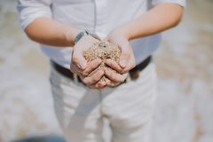 Shallow Focus Photography of Person Holding Brown Sand Royalty Free Stock Photography