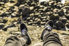 Shallow Focus Photography of Person Wearing Gray Jeans Sitting in Front Rocks Royalty Free Stock Photos