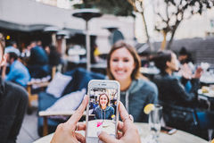 Shallow Focus Photography of Silver Iphone 6 Showing Woman in Blue Hoodie Royalty Free Stock Photos