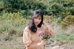Shallow Focus Photography of Woman in Beige Off-shoulder Dress Holding Bouquet of Flowers Stock Image