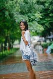 Shallow Focus Photography of Woman in White Shirt and Blue Denim Shorts on Street Near Green Trees royalty free stock photos