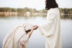 Shallow focus shot of a female grabbing the hand of Jesus Christ for healing and help