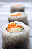 Shallow focus vertical macro of 3 rolls of sushi Royalty Free Stock Image