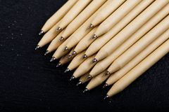 Shallow focus view of a close-up image of new pen pencils seen on dark black background. mock up. Detail of some of the beige pen pencil tips is evident, seen on royalty free stock image