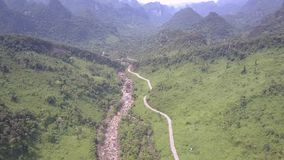 Shallow mountain stream flows beside narrow curving road