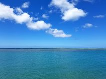 Shallow ocean waters off Maunalua Bay Beach Park. Looking into the pacific ocean with clouds in the air stock photos