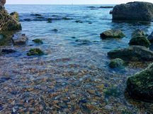 Seascape with shallow water. The shallow water, pebble and rocks Royalty Free Stock Photos