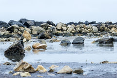 Shallow waters on rocky beach. Sea shallow water and rocks Royalty Free Stock Photo