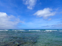 Shallow wavy ocean waters with coral beneath of Waikiki looking. Into the pacific ocean with a clear blue sky on Oahu stock photos