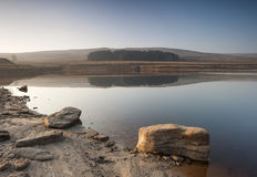 Shallow Yorkshire moorland reservoir. Millstone grit boulders along the exposed shoreline of a low yorkshire moorland waterfall stock photo