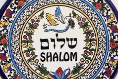 Shalom peace. Decorative plate with the image of a dove carrying an olive branch and inscription peace in Hebrew and English Royalty Free Stock Image