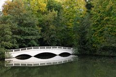 Sham white wooden bridge by lake Stock Photos