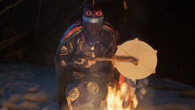 The shaman beats his drum sitting near the fire.