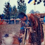 Shaman on a fire. Shaman bent over the fire, breathing in the smoke. (gathering of shamans on Olkhon Island Royalty Free Stock Image